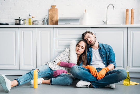 tired couple sitting on floor and leaning on kitchen counter after cleaning in kitchen