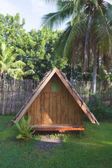 Houses made of wood. Bungalow with a roof made of palm leaves against the backdrop of a fence of bamboo and palm trees