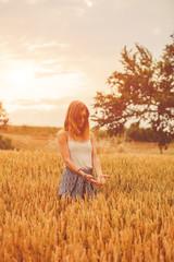 Girl enjoying in a golden wheat - field in the summer.