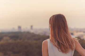 Single woman looking at the distant city landscape.