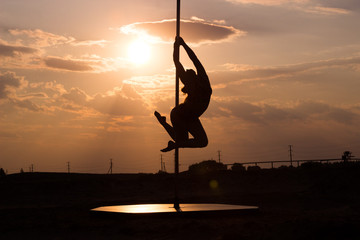 Pole dancer girl perfoms a trick on a pilon on sunset sky