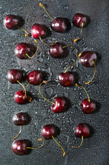 red cherry scattered on a black table