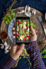 Woman hands take smartphone food photo of cauliflower vegetables salad. Phone food photography for social media or blogging in popular and trendy top view style. Raw vegan vegetarian meal concept.