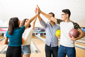 Friends Giving High-Five While Holding Bowling Balls