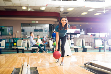 Teenage Girl Throwing Ball While Training For Bowling