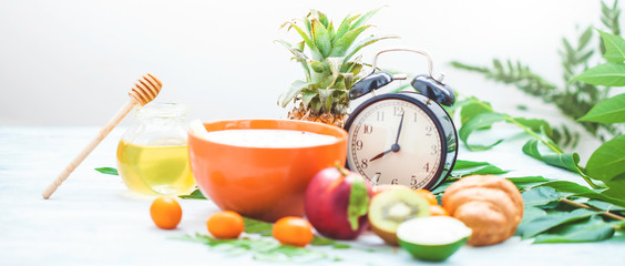 morning breakfast, muesli, fruit, peaches, honey and pineapple on a light background with green leaves Awakening with an alarm clock Healthy breakfast freshness Copyspace Banner concept