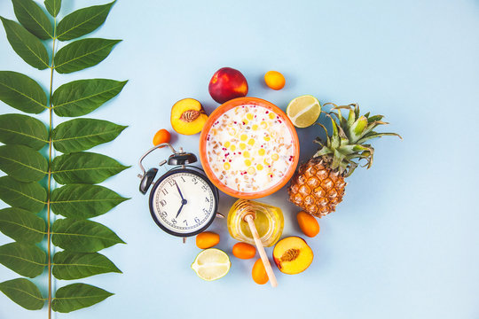 morning breakfast, muesli, fruit, peaches , ananas ,honey on a blue background with green leaves Awakening with an alarm clock Healthy breakfast freshness Flat lay Top view Copyspace