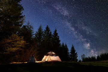 Silhouette of male hiker sitting alone near tourist tent at campfire on valley, enjoying night blue starry sky, Milky way, pine trees forest on background. Beauty of nature, mountain camping concept