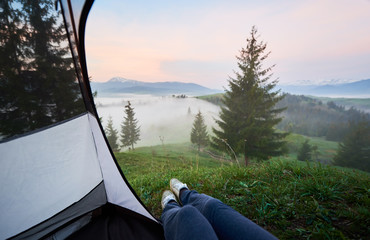 View of foggy valleys, pine forest and distant mountains with snowy peak from inside of tourist tent with woman legs in jeans and running shoes on first plan. Tourism, camping and recreation concept.