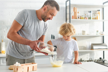 man pouring flour into bowl while his son whisking eggs at kitchen