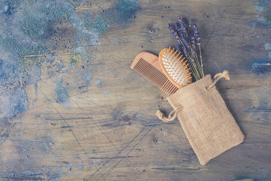 Wooden Scalp and Massage brush and hair comb with natural lavender on the rustic background