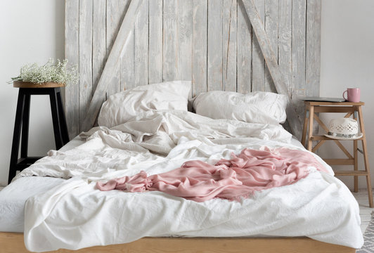 Soft home interior. Bed, white and pink bedspreads, old wood headboard. Cozy mornung