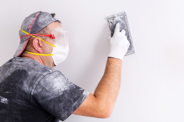 Plasterer wearing dust mask and googles at wall polishing. House renovation concept.