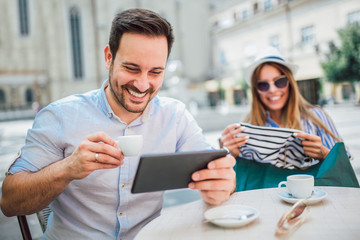 Beautiful loving couple sitting in a cafe enjoying in coffee and conversation after shopping, using digital tablet