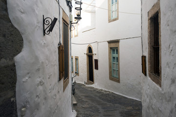 A view of a narrow street with arch and wooden windows and doors with white wall stone...