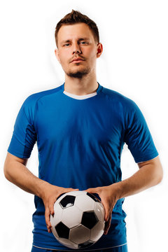 Young handsome football player holds in hands soccer ball posing on white isolated.