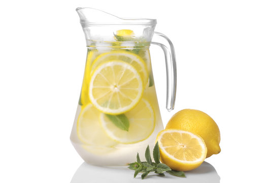 Homemade lemonade with mint and ice in a glass jug and a glass next to fresh lemon on a white background. isolated...