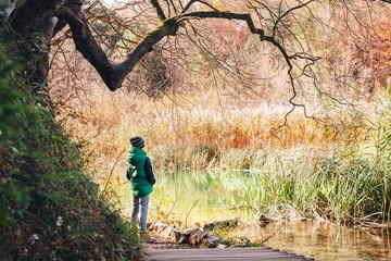Boy stay  under big tree near the pond in autumn park