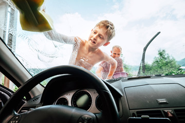 Car washing process: son helps his father to wash a car front window