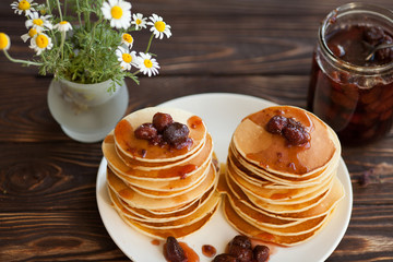 Delicious pancakes on wooden table with strawberry jam