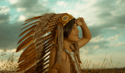 Child playing at sunset dressed as an American Indian, wearing an Indian feather plume and breastplate. Field of wheat and nature