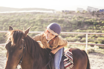 ride with a helmet for a beautiful attractive young woman with nice smile. jeans and casual clothes for outdoor girls in leisure activity with brown horse. animal therapy for alternative medicine