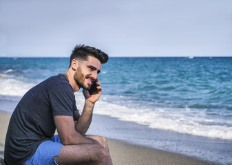Athletic man at the seaside using cell phone to call someone with the sea behind him, sitting on a rock