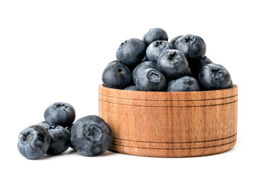 Ripe blueberries in a wooden plate and scattered on a white, isolated.