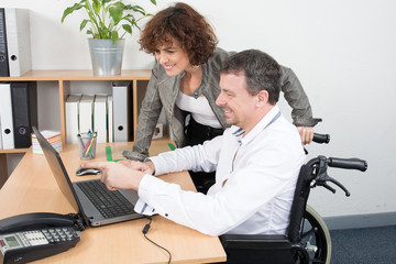 wheelchair businessman at office with pretty businesswoman team work