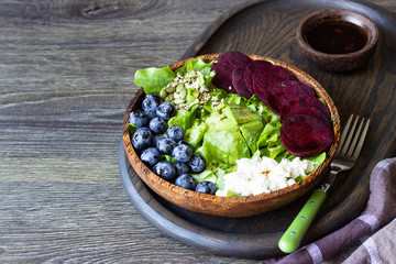 Fresh healthy salad lettuce with avocado, blueberry, beetroot and mozzarella in a brown wooden bowl.