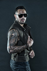 Bearded man with tattoo on strong arms. Tattoo model with beard on unshaven face. Tattooed man with biceps and triceps. Fashion macho in trendy sunglasses. Fashion style and trend, vintage filter
