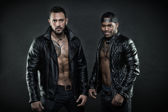Bikers with sexy bare torsos. Fashion models in leather jackets. Rock stars with tattooed chests and muscular bodies. Smiling African man and brutal Caucasian guy isolated on black background