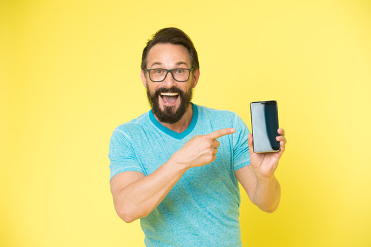 Check out new app. Guy eyeglasses cheerful pointing at smartphone. Man happy user recommends try application for smartphone. Man takes advantages online communication. Guy bearded smartphone user