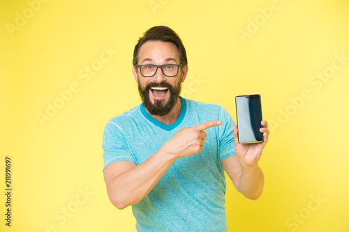 Check out new app  Guy eyeglasses cheerful pointing at smartphone
