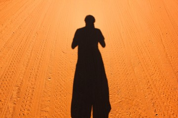Self shadow on orange, brown dirt path in the middle of nowhere in Outback Australia. Alone in hot desert, arid area concept
