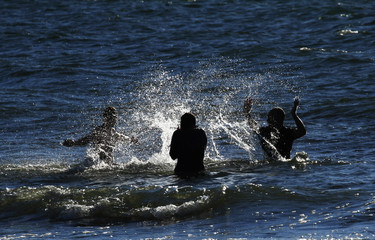 Three friends splashing water against each other in the sea in Gotland, Sweden.