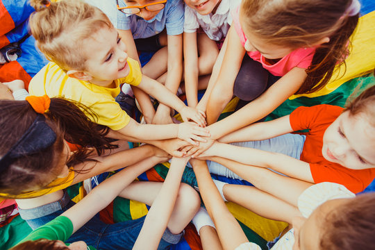 Group of children putting their hands together