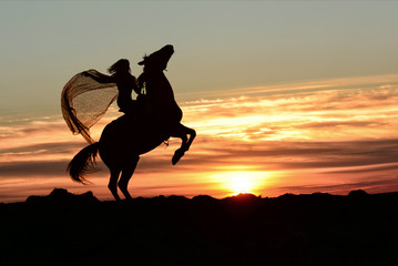 Rearing up horse, queen rider with mantle riding a horse stallion to fantasy clouds on sunset. Equine and girls silhouette jumping on peak mountain with cloudy sky.
