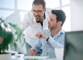 business colleagues discussing business issues near the desktop
