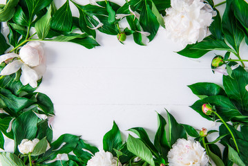 Floral wreath frame with white peony flowers and green leaves on white wooden background. Flat lay, top view. Selective focus, copy space.