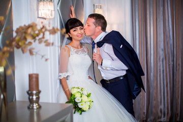 Beautiful bride in white wedding dress is standing near wall, groom is standing next to her and kisses her on cheek