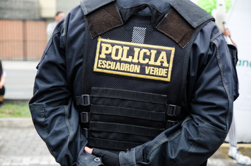 Back of a male police officer, uniform of a policeman in Peru, on his back says police squadron green, security concept