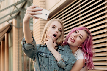 Friends taking selfie with a smart phone and making faces and fun. Closeup of girls making funny faces and smiling for selfie. Two happy girlfriends taking photo with their smartphone in the city