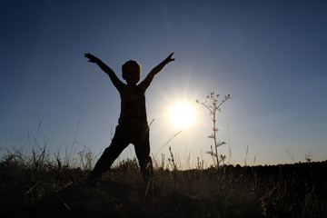 Silhouette of a boy with his hands up in the pose of a rune man. The child joyfully meets the dawn of the sunrise.