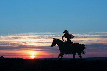 Cowboy postman running in rays of the setting sun and hold the hat on head. Western concept.