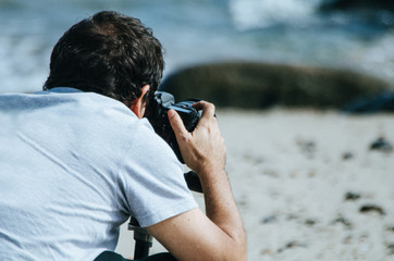 Traveling and photography. Young man with camera taking picture on the sea beach.