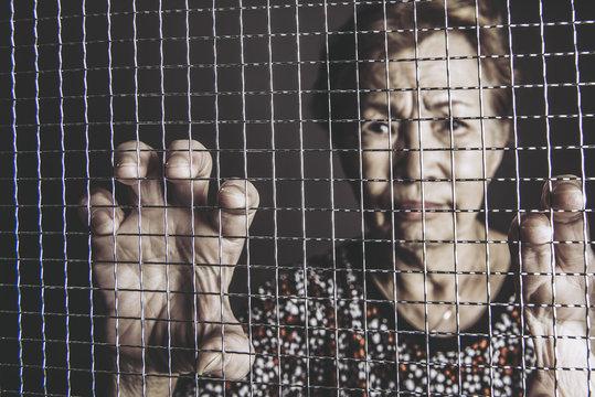 網目をつかむ高齢女性