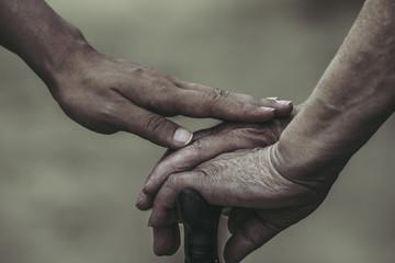 杖を持つ女性に手を添える女性