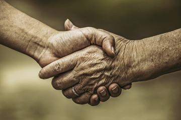 高齢女性と若い女性の握手
