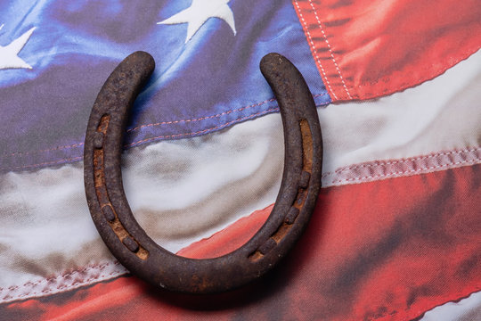 Rusty old horseshoe on USA flag background with room for text